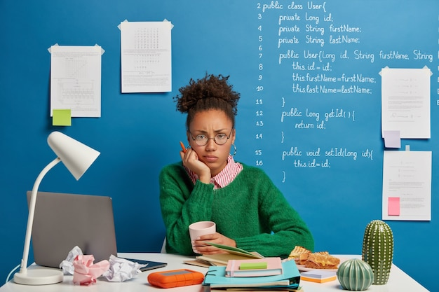 Mulher afro descontente segura caneta, sente-se cansada da preparação para o exame, bebe café e olha tristemente para a câmera, senta-se na mesa de casa com os equipamentos necessários e o bloco de notas