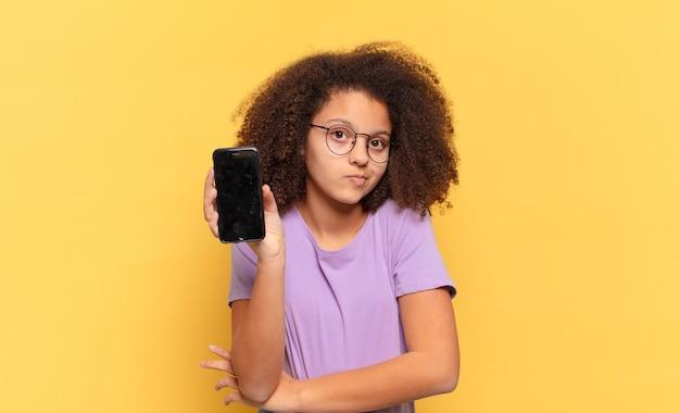 Mulher afro encolhendo os ombros, sentindo-se confusa e insegura, duvidando com os braços cruzados e olhar perplexo e segurando um celular