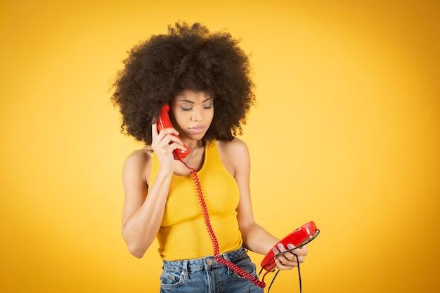 Mulher afro falando no telefone fixo