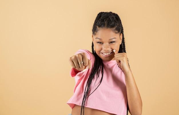 Mulher afro fazendo gesto de soco em fundo amarelo