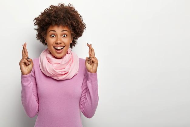 Mulher afro feliz e esperançosa com os dedos cruzados, deseja sorte na entrevista de emprego, usa gola alta roxa e lenço de seda