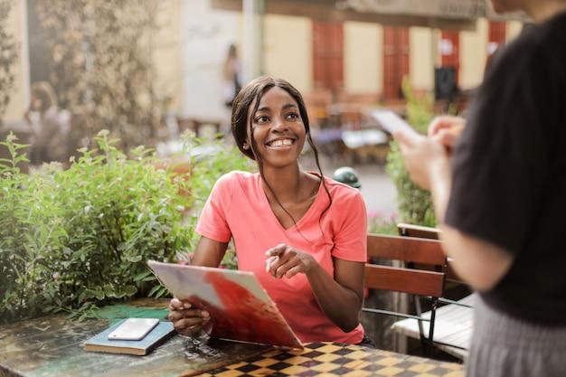 Mulher afro feliz em um bistrô
