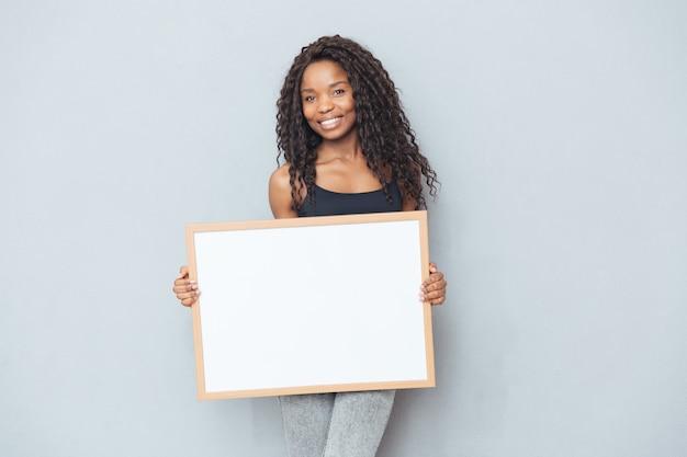 Mulher afro feliz mostrando um quadro em branco sobre uma parede cinza