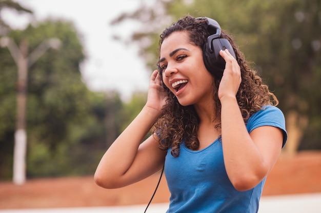Mulher afro feliz ouvindo música no fone de ouvido dela.