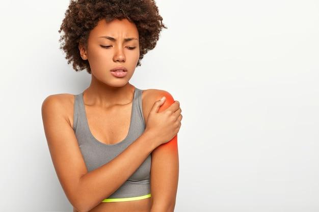Mulher afro insatisfeita toca ombro vermelho, alonga músculos durante o treinamento esportivo, tem expressão triste, usa sutiã cinza