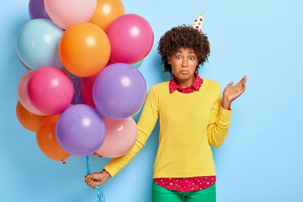 Mulher afro, intrigada e inconsciente, fica parada com balões coloridos, não sabe onde a festa é realizada