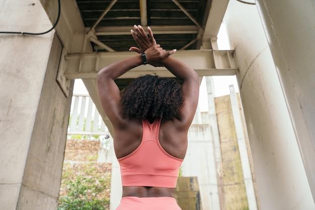 Mulher afro irreconhecível em roupas esportivas rosa. visão horizontal de mulher fitness alongando-se ao ar livre