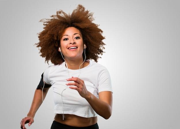 Mulher afro jovem fitness, correr e ouvir música