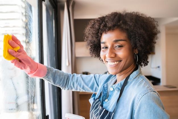 Mulher afro limpando janela com pano em casa
