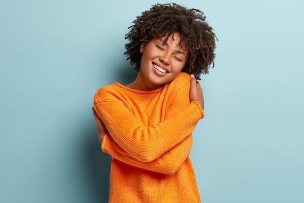 Mulher afro linda e charmosa fica de olhos fechados, sorri de prazer, mostra dentes brancos sente conforto, se abraça, usa blusão laranja, inclina a cabeça, modela sobre parede azul, tem autoestima elevada
