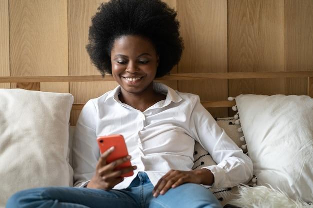 Mulher afro-milenar alegre deitada na cama em casa, descansando, usando telefone celular, digitando mensagem