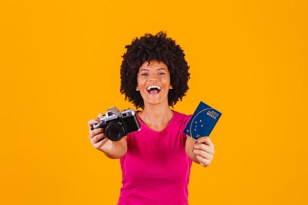 Mulher afro mista com câmera fotográfica e passaporte brasileiro