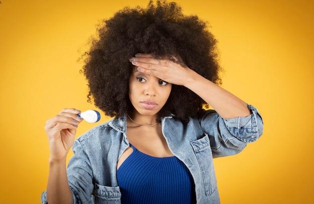 Mulher afro mista com febre, medindo a febre com um termômetro digital