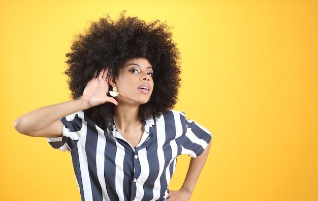 Mulher afro-mista, com problemas auditivos, mão na orelha, fundo amarelo