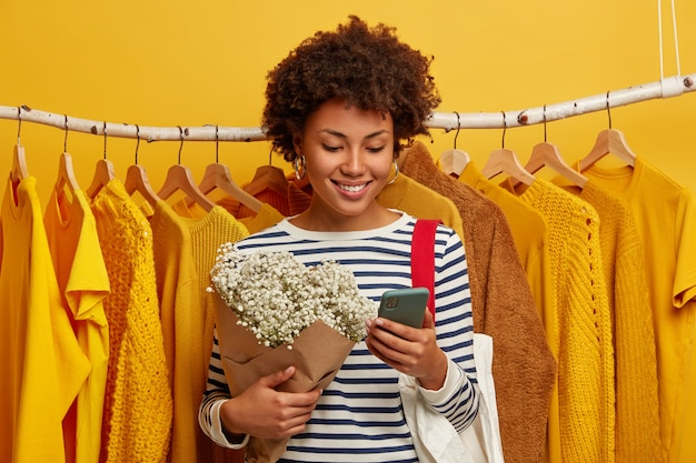 Mulher afro muito feliz focada no dispositivo smartphone, segura um lindo buquê, sorri com alegria, fica perto de uma roupa amarela pendurada em cabides.