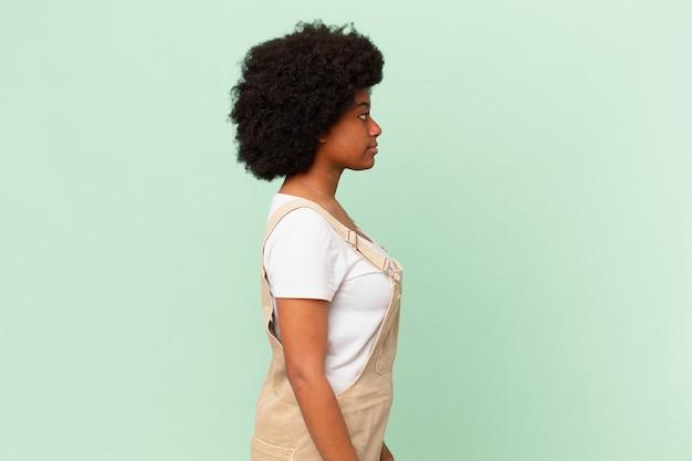 Mulher afro na vista de perfil, olhando para copiar o espaço à frente, pensando, imaginando ou sonhando acordado com o conceito do chef