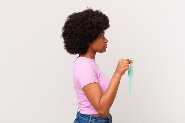 Mulher afro na vista de perfil, olhando para copiar o espaço à frente, pensando, imaginando ou sonhando acordado conceito de relógio