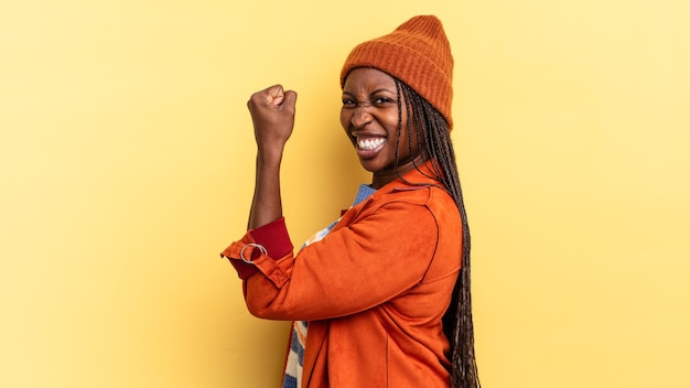 Mulher afro negra bonita se sentindo feliz, satisfeita e poderosa, flexionando a forma e bíceps musculosos, parecendo forte depois da academia