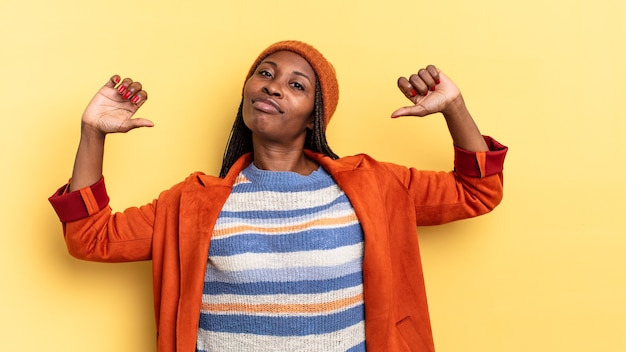 Mulher afro negra bonita se sentindo orgulhosa, arrogante e confiante, parecendo satisfeita e bem-sucedida, apontando para si mesma