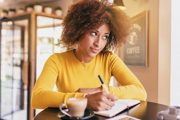 Mulher afro nova no café, está pensando sobre uma ideia para escrever.
