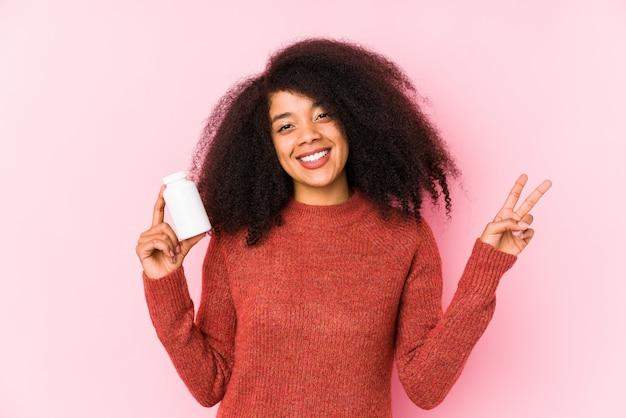 Mulher afro nova que mantem vitaminas isoladas mulher afro nova que mantem uma vitaminajovem e despreocupada mostrando um símbolo de paz com os dedos.