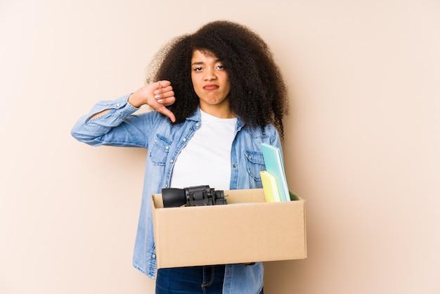 Mulher afro nova que move-se em casa isolada mulher afro nova que mostra um gesto do desagrado, polegares para baixo. conceito de desacordo.