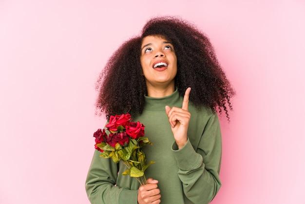 Mulher afro nova que prende rosas isoladas mulher afro nova que prende um rosespointing de cabeça com boca aberta.