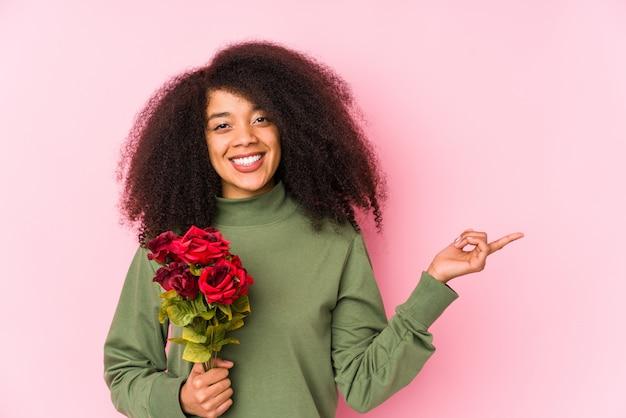 Mulher afro nova que prende rosas isoladas mulher afro nova que prende um rosessmiling e apontar de lado, mostrando algo no espaço em branco.