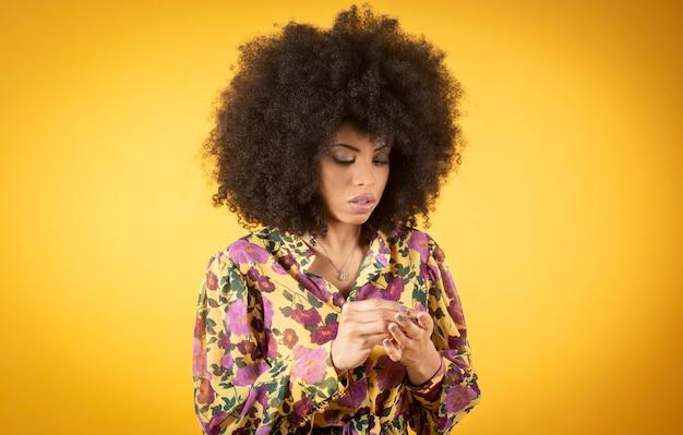 Mulher afro olhando para as unhas