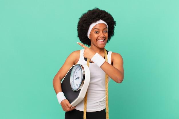 Mulher afro parecendo animada e surpresa, apontando para o lado e para cima para copiar o conceito de dieta espacial