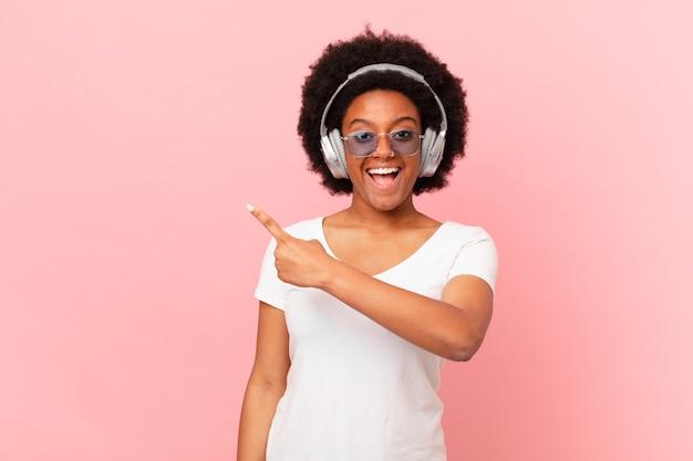 Mulher afro parecendo animada e surpresa, apontando para o lado e para cima para copiar o espaço. conceito de musica