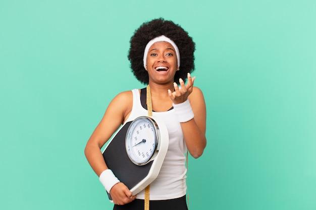 Mulher afro parecendo desesperada e frustrada, estressada, infeliz e irritada, gritando e gritando conceito de dieta
