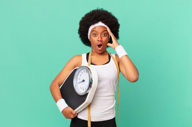 Mulher afro parecendo feliz, atônita e surpresa, sorrindo e percebendo o incrível e incrível conceito de boas notícias