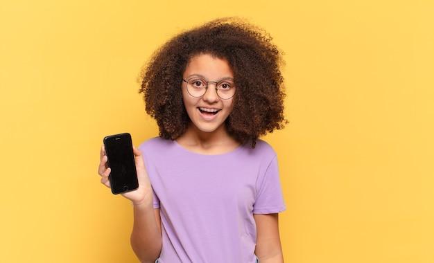 Mulher afro parecendo feliz e agradavelmente surpresa, animada com uma expressão fascinada e chocada e segurando um celular