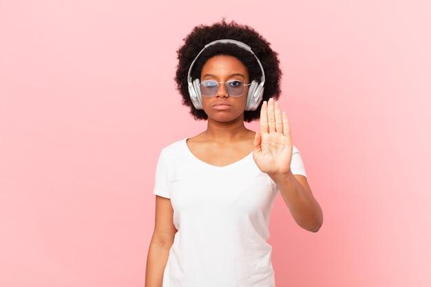 Mulher afro parecendo séria, severa, descontente e com raiva, mostrando a palma da mão aberta, fazendo gesto de parada. conceito de musica