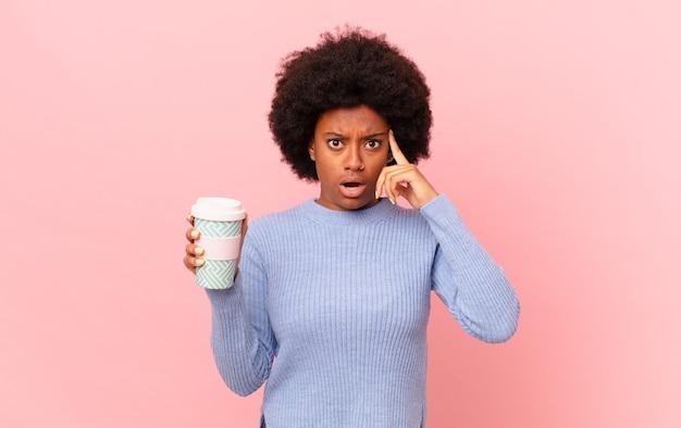 Mulher afro parecendo surpresa, boquiaberta, chocada, percebendo um novo pensamento, ideia ou conceito. conceito de café