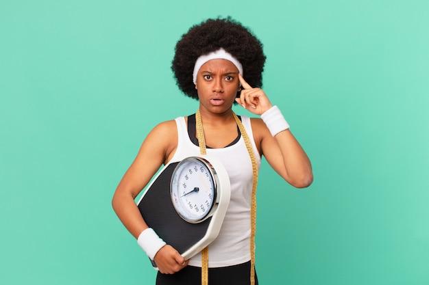 Mulher afro parecendo surpresa, boquiaberta, chocada, percebendo um novo pensamento, ideia ou conceito de conceito de dieta