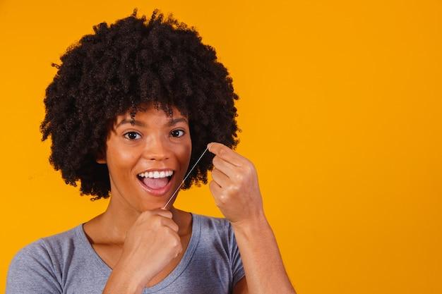 Mulher afro passando fio dental nos dentes. conceito de saúde bucal