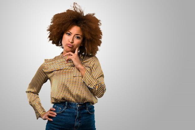 Mulher afro pensativa, tendo dúvidas