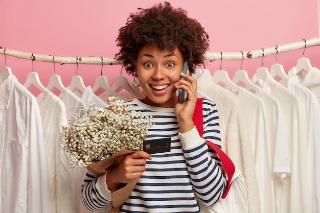 Mulher afro positiva faz pedidos online, liga pelo celular, usa cartão de crédito para fazer compras, olha feliz para a câmera