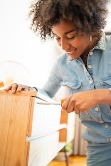 Mulher afro que repara móveis em casa.