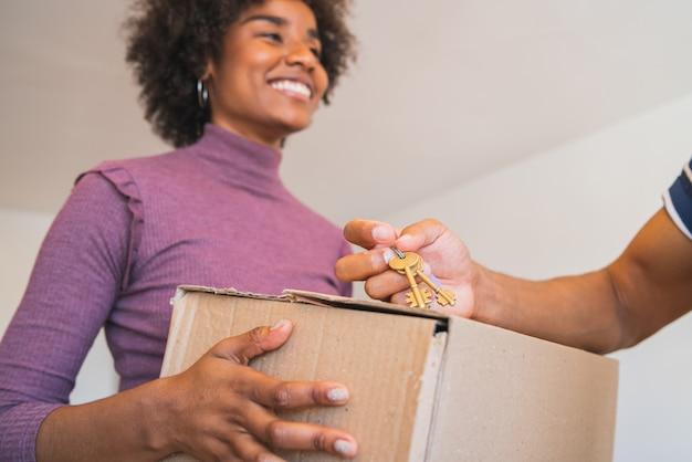 Mulher afro, recebendo um pacote em casa.