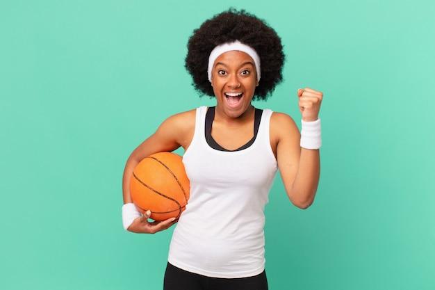 Mulher afro se sentindo chocada, animada e feliz, rindo e comemorando o sucesso, dizendo uau !. conceito de basquete