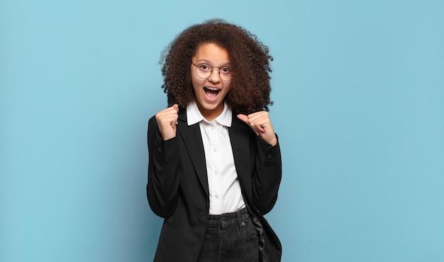 Mulher afro se sentindo chocada, animada e feliz, rindo e comemorando o sucesso, dizendo uau !. conceito de negócio humorístico