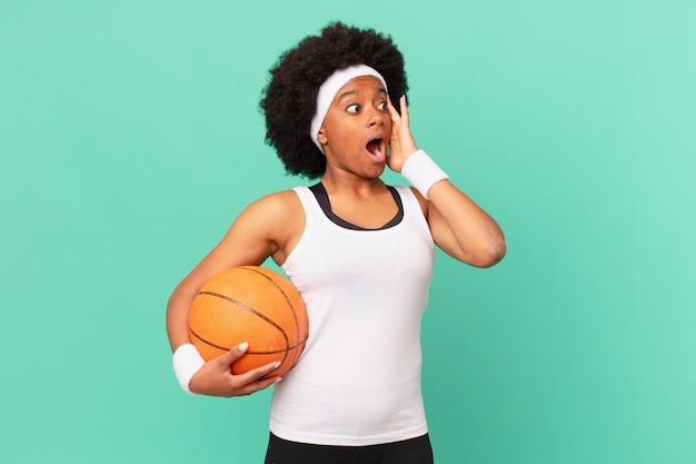 Mulher afro se sentindo feliz, animada e surpresa, olhando para o lado com as duas mãos no rosto. conceito de basquete