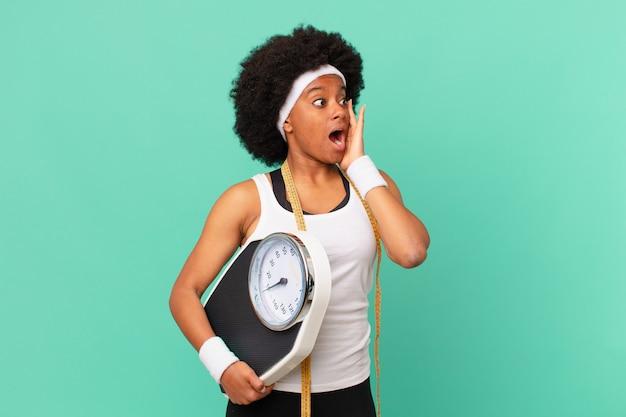 Mulher afro se sentindo feliz, animada e surpresa, olhando para o lado com as duas mãos no rosto conceito de dieta