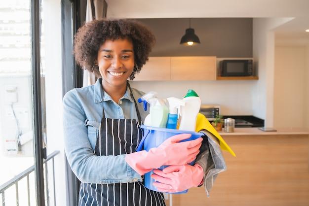 Mulher afro segurando um balde com produtos de limpeza