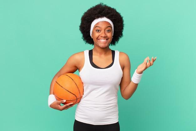 Mulher afro sentindo-se feliz, surpresa e alegre, sorrindo com atitude positiva, percebendo uma solução ou ideia. conceito de basquete