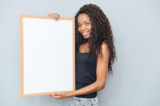 Mulher afro sorridente mostrando um quadro em branco sobre uma parede cinza