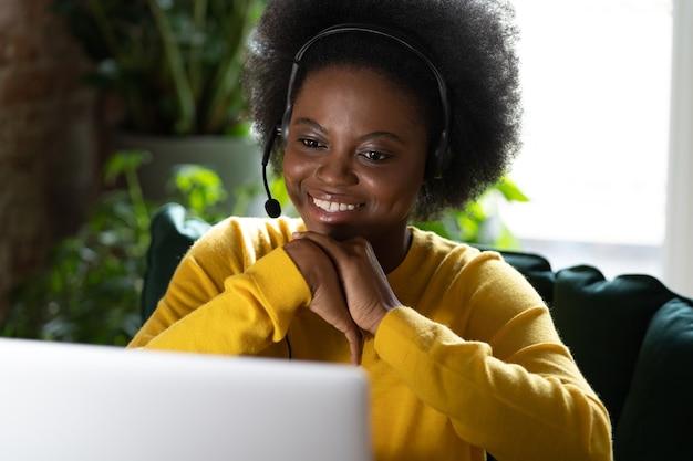 Mulher afro sorridente usando fones de ouvido, fala por videochamada, usando um laptop, assistindo ao webinar trabalhar de casa
